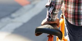 photo d'un jeune homme que l'on voit de dos poussant un vélo